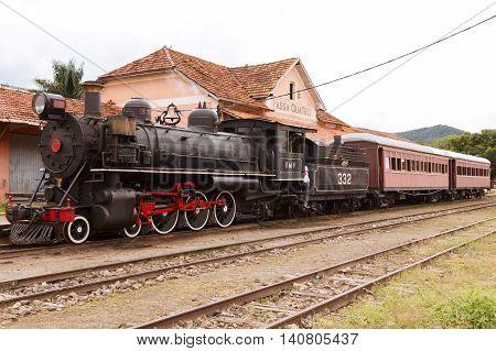 PASSA-QUATRO MINAS GERAIS/BRAZIL- March 21: Train station with locomotive in rainy day on March 21 2015 in Passa-Quatro Brazil. It's popular sightseeing tour named Trem Serra da Mantiqueira
