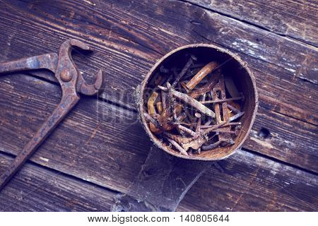 old rusty pinchers with can of nails on wooden boards background