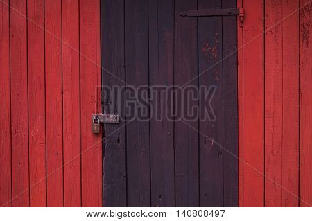 A Pad Locked wooden black door .