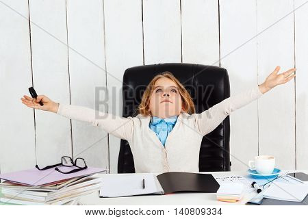 Young beautiful girl sitting at working place, looking up, shruging in office.