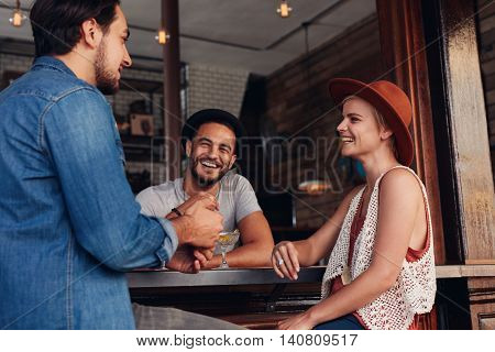 Young men and women sitting together and talking in a coffee shop. Group of young friends hanging out at a cafe.