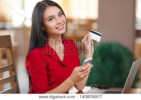 Young business woman holding mobile phone and credit card. Woman pays for a purchase with credit card. Purchase online. Shopping online