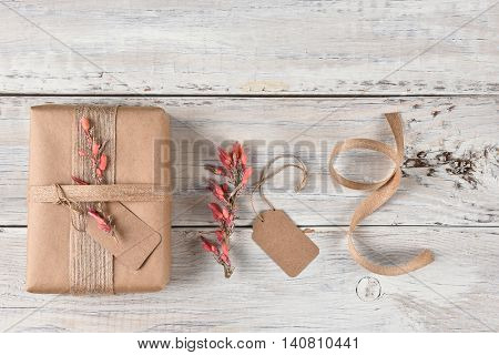 Top view of a Christmas present wrapped with brown paper, burlap ribbon and flowers, next to gift tag flowers and ribbon.