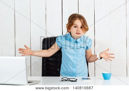 Young beautiful girl shruging hands at working place, looking to camera in office.