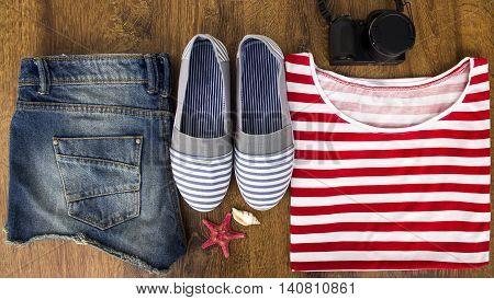 Set clothes for going to sea: jeans shorts a striped shirt and striped sneakers photocamera shells a top view of a wooden background