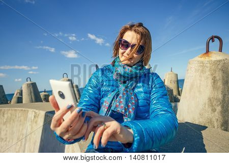 young woman taking self portrait on smartphone