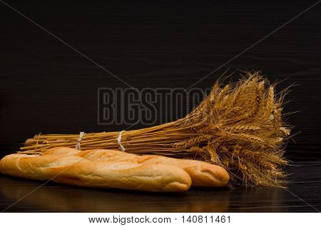 Two white loaf and a sheaf on a black background with space for text
