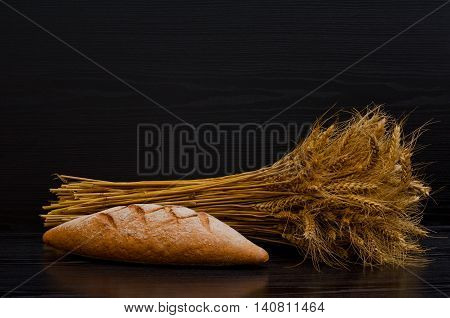 Sheaf and a bread on a black background with space for text