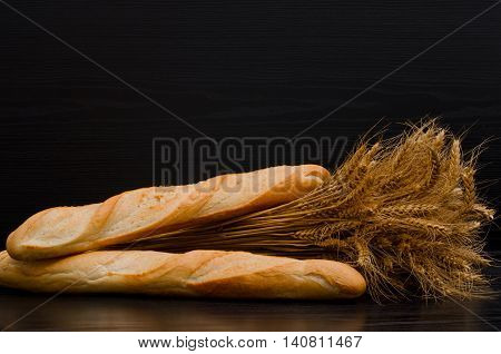 Sheaf and two white loaf on a black background with space for text