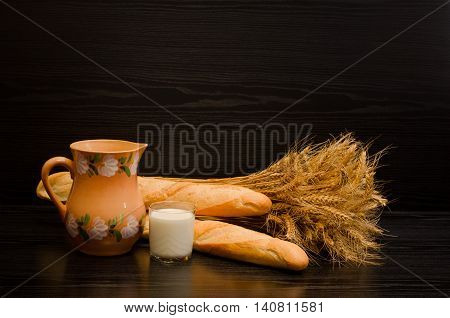 A glass of milk a pitcher and loaves sheaf on a black background with space for text
