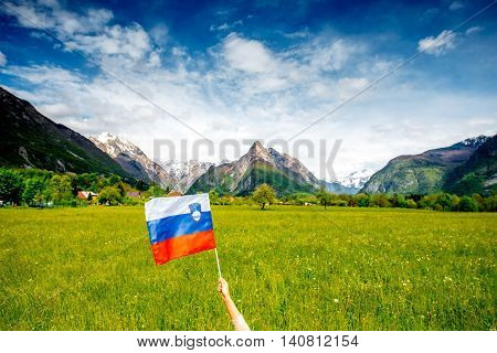 Beautiful mountain landscape with female hand holding slovenian flag. Traveling in Triglav national park in Slovenia