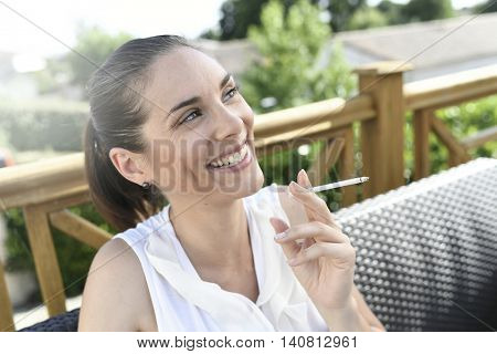 Portrait of smiling girl smoking a cigarette