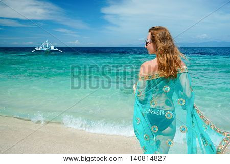 young caucasian woman with blue sari is staying on the white beach of tropical turcuoise sea at sanny day and getting plesaure under blue sky
