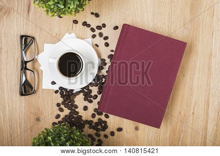 Top view of wooden surface with coffee cup on napkins beans glasses decorative plants and closed hardcover book with copy space
