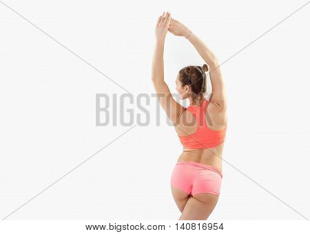 Portrait Of Young Brunette Woman Doing Pilates Stretching Exercises On White Studio Background