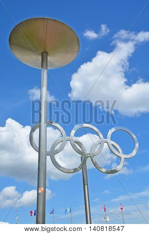 MONTREAL CANADA JULY 30 2016: Montreal Olympic cauldron and olympic rings. Olympic flame is a symbol of the Olympic Games Commemorating the theft of fire from the Greek god Zeus by Prometheus