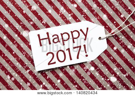 One Label On A Red And Brown Striped Wrapping Paper. Textured Background With Snowflakes. Tag With Ribbon. English Text Happy 2017 For Happy New Year Greetings