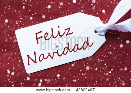 One White Label On A Red Textured Background. Tag With Ribbon And Snowflakes. Spanish Text Feliz Navidad Means Merry Christmas