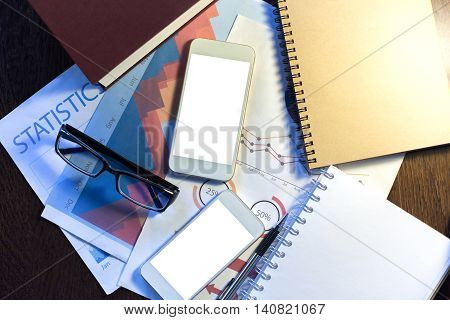 Top view of wooden desktop with two blank white cellular phones glasses business reports closed book and spiral notepad. Mock up