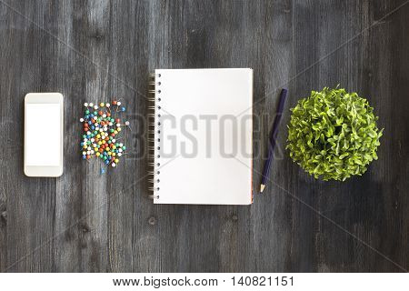 Blank spiral notepad white cellphone colorful pins pencil and plant in the middle of dark wooden desktop. Top view Close up Mock up