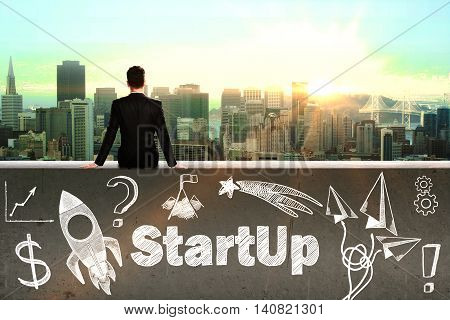Startup concept with sitting businessman looking at city and rocket ship sketch on concrete wall