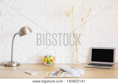 Creative desktop with blank laptop screen sketches smart phone lamp wheat spikes and other items on white brick wall background. Mock up