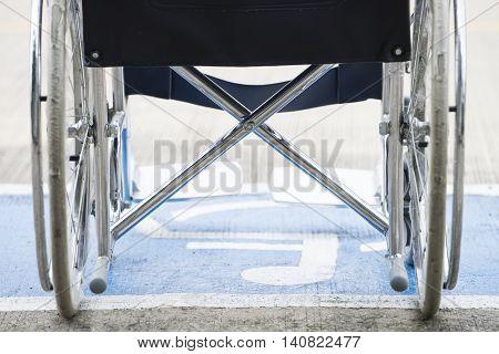 Pavement handicap symbol and wheelchair, close up