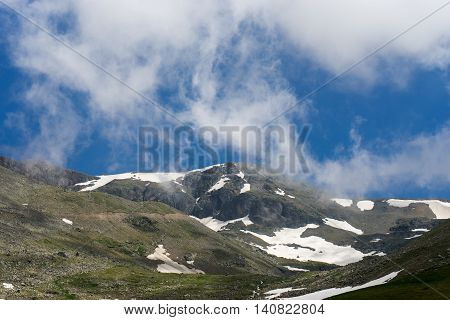 High Mountain Ridge And Snow Rocks Under The Blue Sky And White Clouds And Mist.