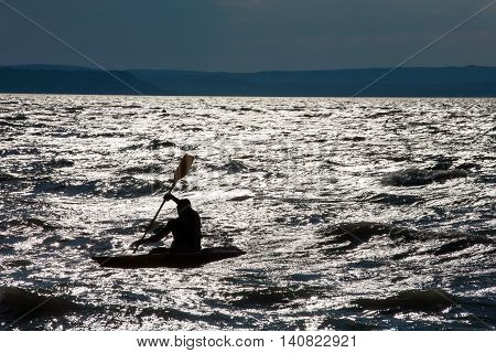 Kayakers Silhouette in silvery water at sunset in the backlight. (Lake Balaton Hungary)