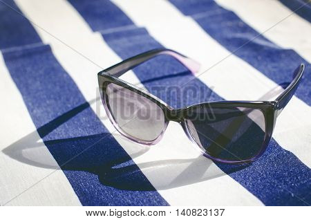 Black mirrored sunglasses on a blanket. Shadow from glasses. Sunlight. Summer concept