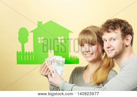 Wife And Husband Holds Paper House.