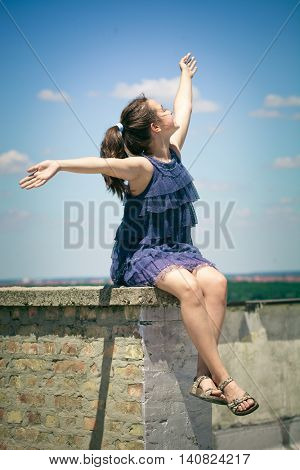 happy smiling  girl in blue  dress  sit on roof with arms up summer day