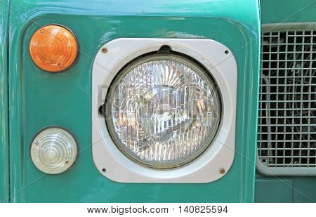Close up image of headlight of green vintage car