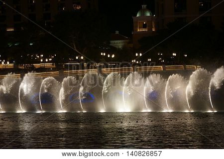 LAS VEGAS, USA - DECEMBER 23: The famous fountain show in front of the Bellagio luxury hotel with water fountains and colorful lighting on Las Vegas Boulevard on the night of December 23, 2015 in Las Vegas.
