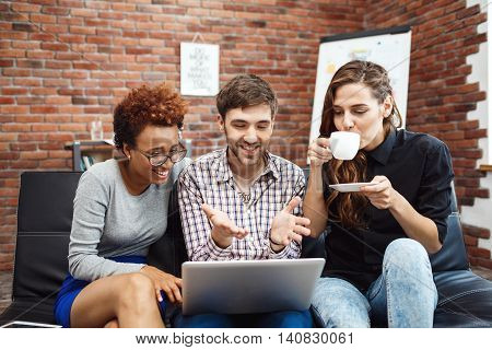 Colleagues rejoicing their work, looking on laptop screen at business meeting.