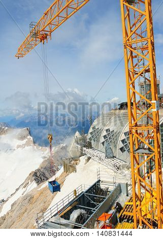 ZUGSPITZE GERMANY - JULY 5, 2016: Unidentified worker and Liebherr crane 150 EC-B on Germany's highest construction site in 2962m. Building the new Zugspitze cable car for tourists and skiers.