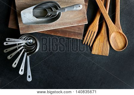 A collection of vintage baking and cooking supplies wood cutting boards and spoons and antique silver measuring cups frame a black slate chalkboard background.