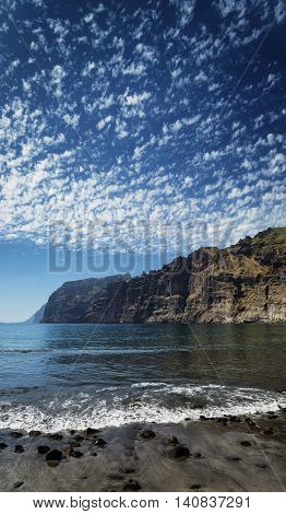 los gigantes cliffs nature landmark and volcanic black sand beach in south tenerife island spain
