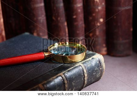 Vintage library. Magnifying glass on old book background
