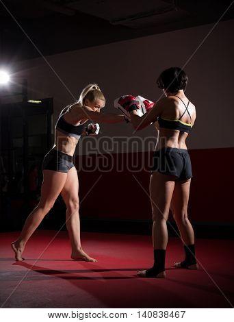 Two kickboxers women in sports hall