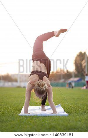 Young blonde woman practicing yoga outdoors. Three Legged Downward Facing Dog.