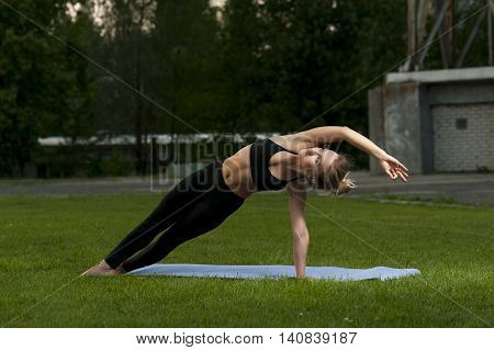 Young caucasian woman in black sportswear practicing yoga outdoors. Side Plank Pose.