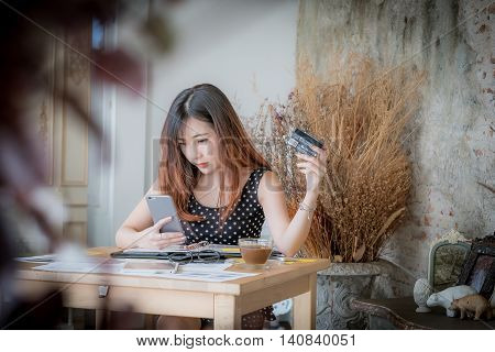 Cute Young Woman Shopping Online With Her Credit Card And A Tablet Computer