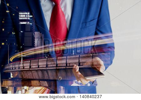Double Exposure Of Businessman Using Mobile Phone Dissolved With Long Shutter Speed Night Cityscape