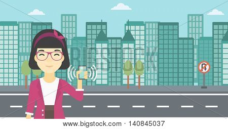 An asian woman holding ringing mobile phone on a city background. Woman answering a phone call. Woman with ringing phone in hand. Vector flat design illustration. Horizontal layout.