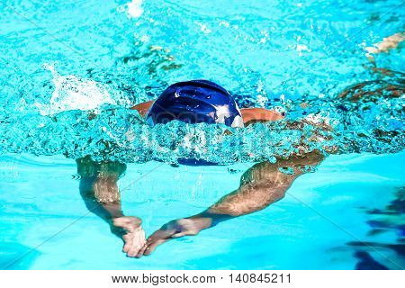 Action photograph of a male swimmer performing the Butterfly Stroke during a race.
