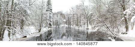 A wintery scene that includes a frozen river and snowy forest.