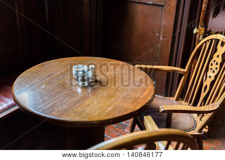 interior and objects concept - close up of vintage pub table and chairs in irish pub or cafe