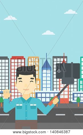 An asian man making selfie with a selfie-stick. Man taking photo with cellphone and waving on a city background. Vector flat design illustration. Vertical layout.