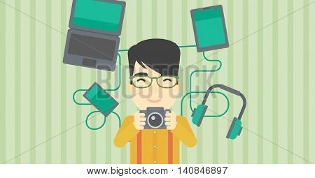 An asian young man taking photo with digital camera. Man surrounded with gadgets. Man using many electronic gadgets. Vector flat design illustration. Horizontal layout.